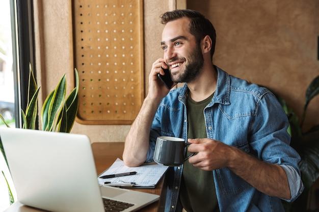 Gut aussehender unrasierter mann mit jeanshemd, der am handy spricht und kaffee mit laptop trinkt, während er im café drinnen arbeitet