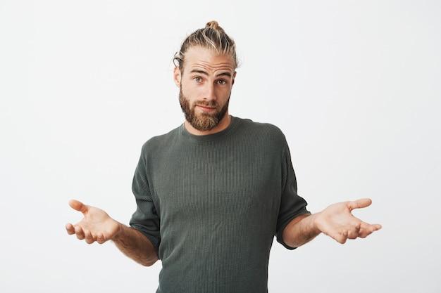 Gut aussehender unrasierter reifer kerl mit stilvollem haarschnitt im grauen stoff, der schaut