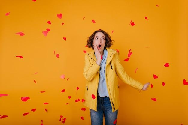 Gut aussehendes blasses mädchen im gelben outfit, das fliegende herzen betrachtet. studioaufnahme einer erstaunlichen lockigen frau in freizeitkleidung, die spaß am valentinstag hat.