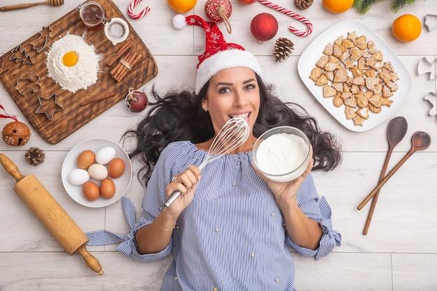 Gut aussehendes dunkelhaariges mädchen, das creme auf rührer schmeckt und auf dem boden liegt und von lebkuchen, eiern, mehl auf einem holztisch, weihnachtsmütze, getrockneten orangen und backformen umgeben ist.