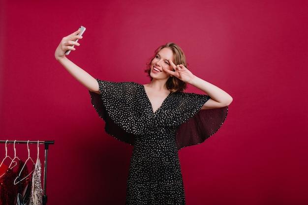 Gut aussehendes junges weibliches modell mit tätowierung, die sich in der umkleidekabine fotografiert