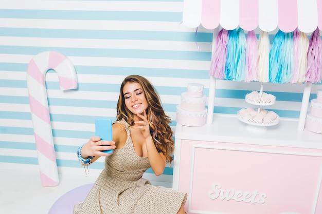Gut aussehendes lockiges mädchen, das vintage-kleid trägt, das selfie vor konditorei mit leckeren süßigkeiten macht. innenporträt der niedlichen fröhlichen frau mit dem blauen telefon, das auf gestreifter wand nahe zähler sitzt.