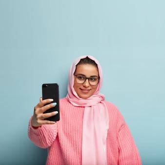 Gut aussehendes mädchen mit sanftem lächeln, schaut gerne auf den bildschirm des geräts, trägt eine rechteckige brille, einen seidenschleier, streckt die hand aus, um einen schönen schuss zu machen, hat maniküre, trägt einen rosa pullover, ist auf blau isoliert