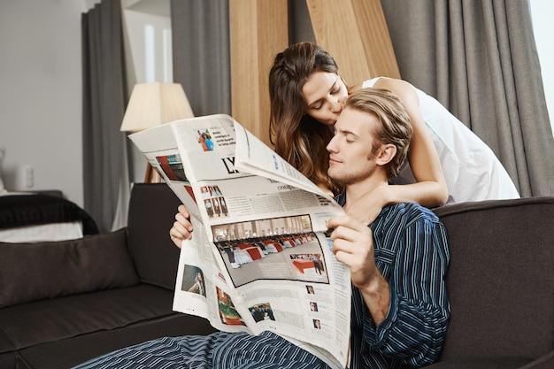 Gut aussehendes paar, das vor dem frühstück zeitung im wohnzimmer liest. hübscher kerl, der nachrichten überprüft, als seine freundin sagt, dass das frühstück fertig ist und küsst kerl zärtlich in die stirn.