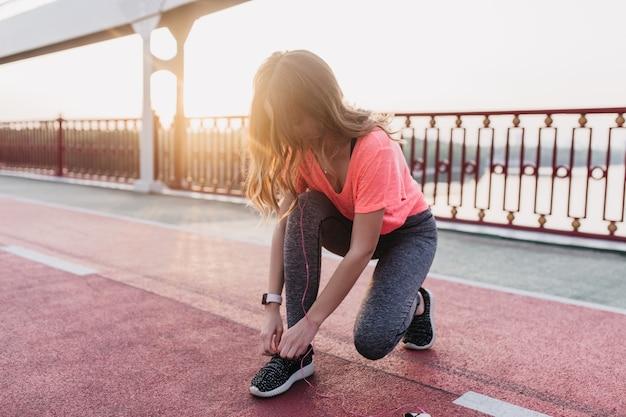 Gut aussehendes weibliches model in trendiger kleidung, die sich auf den marathon vorbereitet. außenaufnahme des brünetten mädchens bindet ihre schnürsenkel am stadion.