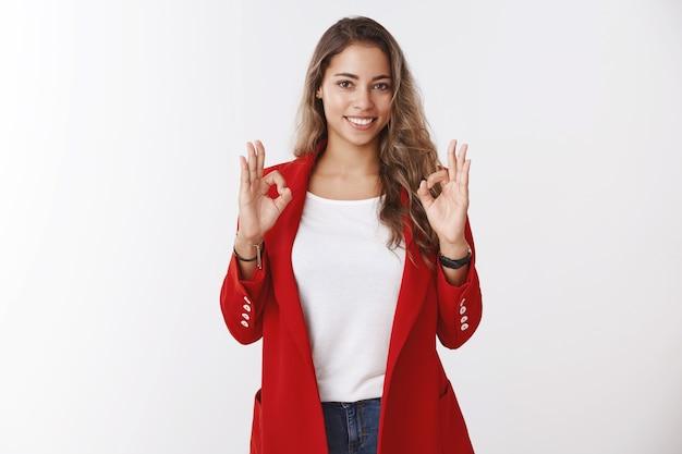 Gut erledigt. studioaufnahme glückliche, selbstbewusste unternehmerin, die eine gute geste zeigt, die selbstbewusst lächelt, total begeistert, zufriedenes gutes ergebnis, lächelt ermutigt, keine sorge um die geste