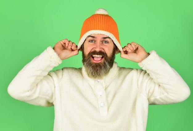 Gut fühlen. bärtiger hipster. hipster-stil. kopf in warmer mütze. gut aussehender mann strickmütze mit bommel. mode-konzept. winterkleidung und accessoires. reifes emotionales hipster-lustiges accessoire.