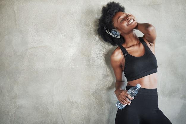 Gut fühlen. porträt des afroamerikanermädchens in der fitnesskleidung, die eine pause nach dem training hat