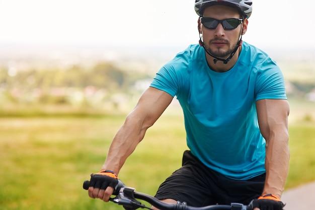 Gut gebauter mann, der fahrrad fährt
