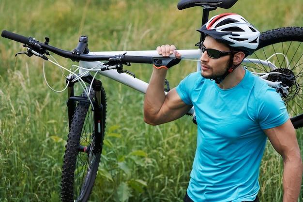 Gut gebauter mann mit seinem fahrrad