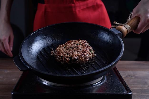 Gut gebratenes stück rindfleisch auf einer gusseisernen grillpfanne in der hand der köchin