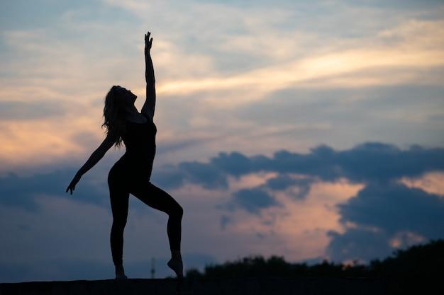 Gut geformte tänzerin auf sonnenaufgang im freien