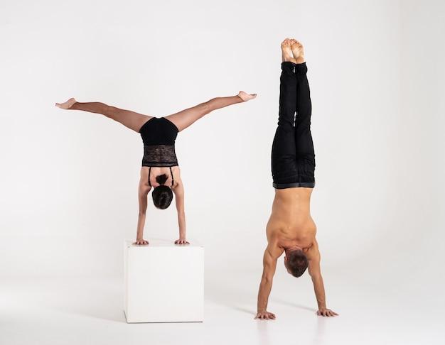 Gut geformter mann und frau, die handstandübung lokalisiert auf weißem hintergrund üben. kraft und motivation.