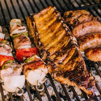 Gut gegrillte fleischstücke und gemüse auf grillkohle