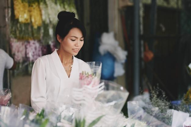 Gut gekleidete asiatische dame, die blumenstrauß im blumenladen wählt