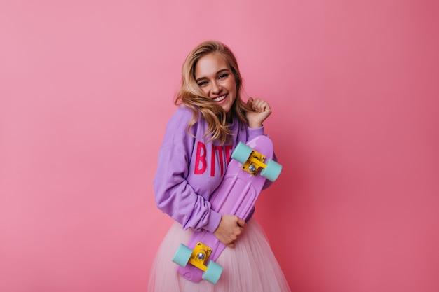 Gut gekleidete dame mit skateboard, die auf rosa backgorund lächelt. inspiriertes kaukasisches mädchen mit blondem haar, das longboard hält.