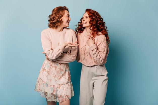 Gut gekleidete damen, die auf blauem hintergrund sprechen. studioaufnahme von ansprechenden mädchen, die sich gegenseitig ansehen.