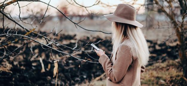 Gut gekleidete elegante dame mit hut, die ein telefon während eines spaziergangs benutzt