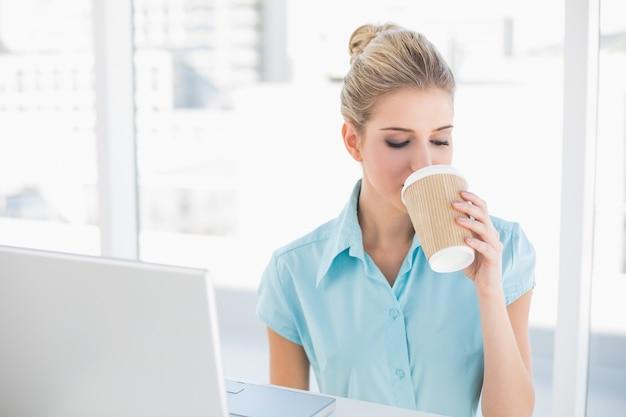 Gut gekleidete geschäftsfrau, die kaffee trinkt