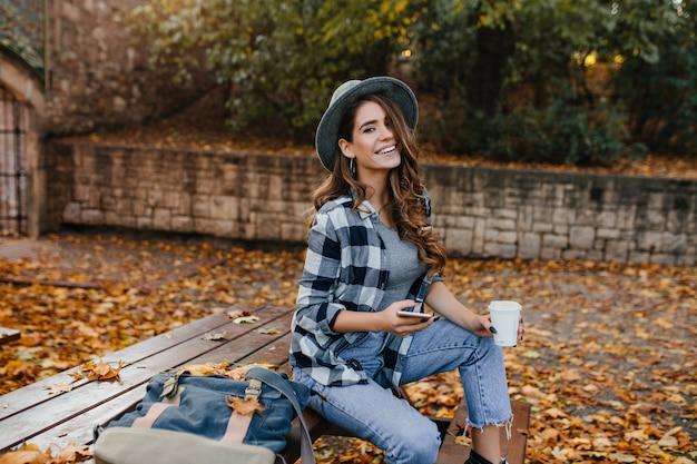 Gut gekleidete lachende frau mit hellbraunem haar, das im oktober im park sitzt und naturansichten genießt