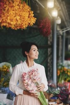 Gut gekleidete schöne asiatin, die mit frischen blumen am markt aufwirft