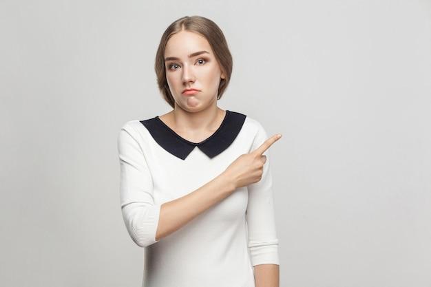 Gut gekleidete schöne frau mit gesammelten haaren, die mit verwirrtem gesicht mit dem finger auf den kopierraum zeigen. studioaufnahme, grauer hintergrund