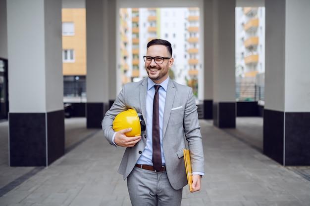 Gut gekleideter architekt im grauen anzug und mit schutzhelm unter der achselhöhle zur arbeit.