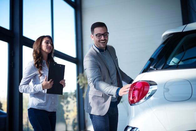Gut gekleideter geschäftsmann, der neues auto kauft, während verkäufer dem kunden neues fahrzeug vorstellt