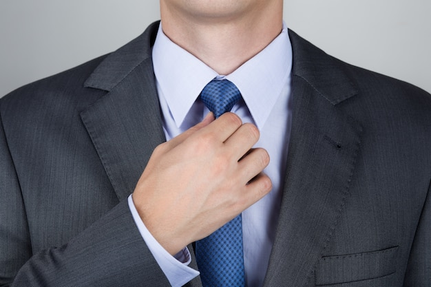 Gut gekleideter geschäftsmann, der seine krawatte anpasst