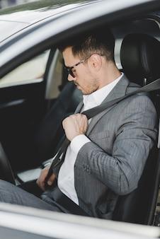 Gut gekleideter junger mann, der sicherheitsgurt im auto bindet