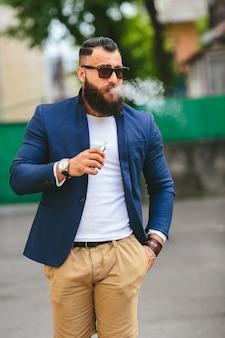 Gut gekleideter mann, der elektronische zigarette raucht