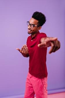 Gut gekleideter positiver typ, der tanzt. stilvolles afrikanisches männliches modell in eleganten gläsern, die auf lila wand aufwerfen.