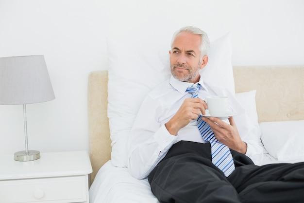 Gut gekleideter reifer mann mit einer tasse tee im bett