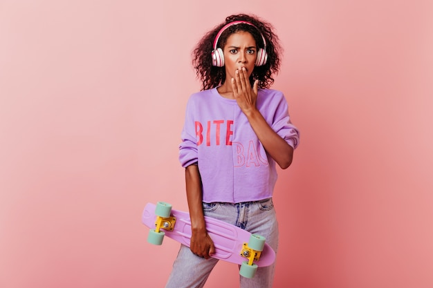 Gut gekleidetes afrikanisches mädchen, das mit longboard aufwirft. porträt der stilvollen schwarzen frau in den kopfhörern, die auf rosa mit schockiertem gesichtsausdruck stehen.