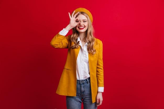 Gut gekleidetes mädchen in der baskenmütze, das gutes zeichen zeigt. weibliches modell in der gelben jacke lokalisiert auf roter wand.