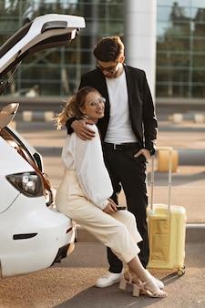 Gut gelaunte frau in weißer bluse und beige hose lächelt und sitzt im auto in der nähe des flughafens