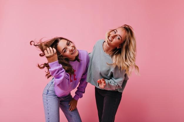 Gut gelaunte freundinnen in jeans, die glück ausdrücken. prächtige schwestern, die über lila lachen.