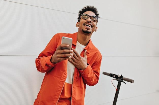 Gut gelaunter brauner lockiger mann mit sonnenbrille, orangefarbener jacke und buntem t-shirt lächelt aufrichtig, hält telefon und posiert in der nähe der weißen wand