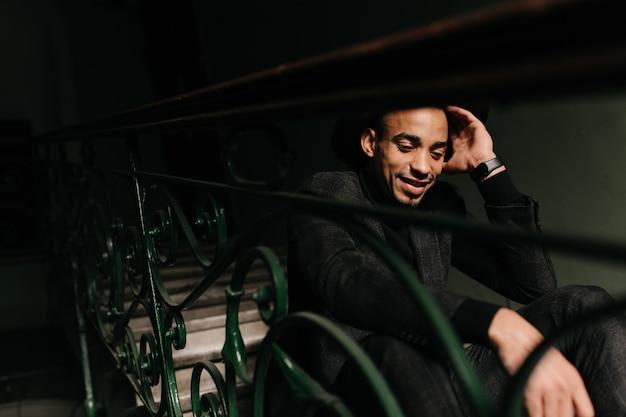 Gut gelaunter, gut gekleideter mann, der auf stufen sitzt. porträt des hübschen afrikanischen kerls, der mit nachdenklichem lächeln aufwirft.