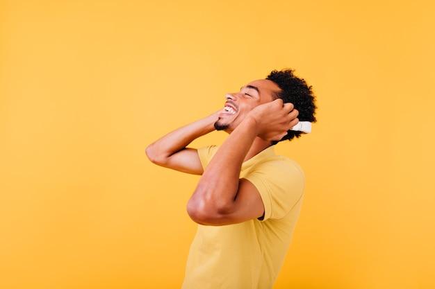 Gut gelaunter junger mann, der lieblingslied mit geschlossenen augen hört. aufgeregter sorgloser afrikanischer typ, der in kopfhörern aufwirft.
