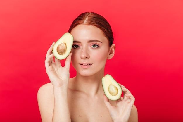 Gut gelauntes mädchen, das geschnittene avocado hält. studioaufnahme der gewinnenden ingwerfrau lokalisiert auf rotem hintergrund.