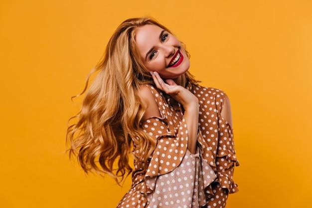 Gut gelauntes weibliches modell, das positive emotionen auf gelber wand ausdrückt. romantische weiße frau im retro-kleid, das während des fotoshootings lacht.