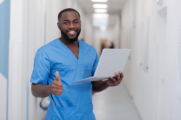 Gut gemacht . fröhlicher junger afroamerikanischer arzt, der im krankenhaus steht, während daumen hoch zeigt und laptop hält