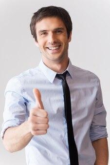 Gut gemacht! glücklicher junger mann in hemd und krawatte, der seinen daumen nach oben zeigt und lächelt