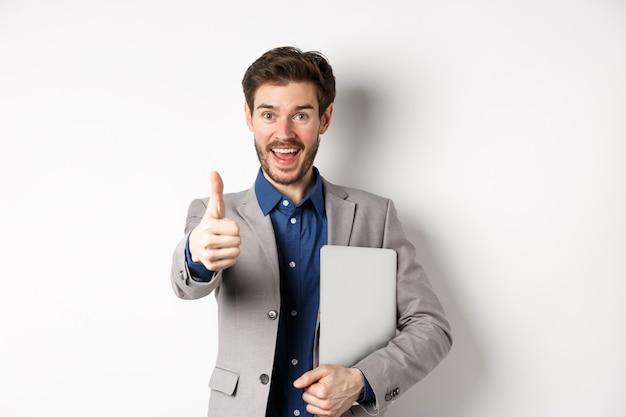 Gut gemacht. glücklicher lächelnder geschäftsmann im anzug, der laptop hält, daumen zeigt, um sie zu preisen, nette arbeitsgeste, stehend auf weißem hintergrund.