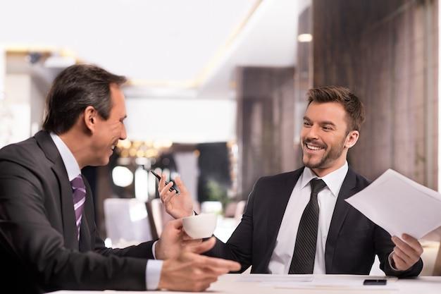Gut gemacht! zwei fröhliche geschäftsleute in abendgarderobe diskutieren etwas und lächeln, während sie im restaurant sitzen