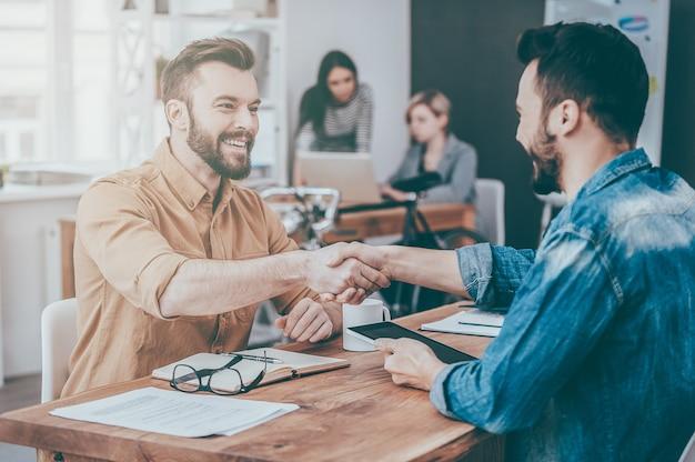 Gut gemacht! zwei selbstbewusste junge männer, die hände schütteln und lächeln, während sie am schreibtisch im büro sitzen, während zwei leute im hintergrund arbeiten