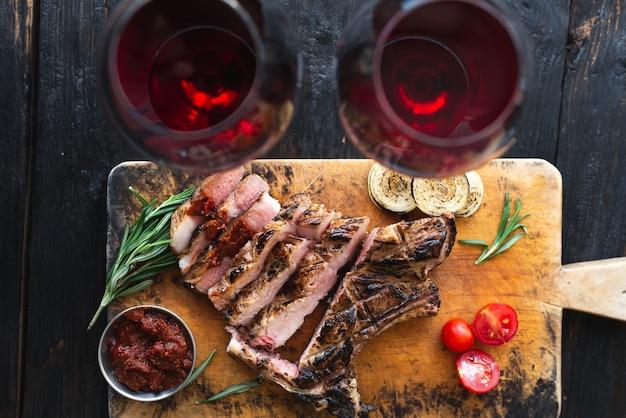 Gut gemachtes steak auf einem schneidebrett, scheiben köstliches aromatisches fleisch, abendessen für zwei personen. zwei gläser rotwein