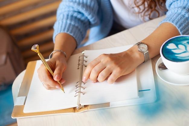 Gut gepflegte frauenhand, die goldstift hält und notizen mit goldstift in notizbuch schreibt, während blauer latte neben fenster trinkt. freiberuflicher journalist, der zu hause arbeitet. zukunftskonzept planen. speicherplatz kopieren