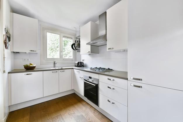 Gut organisiertes kleines wohnkücheninterieur mit waschbecken und hellen möbeln mit herd in städtischer wohnung